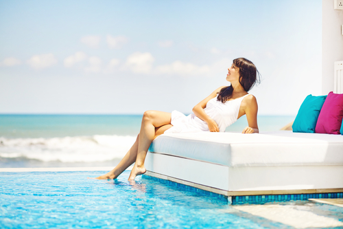 woman lounging on coach by pool