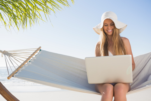 Happy blonde sitting on hammock using laptop at the beach