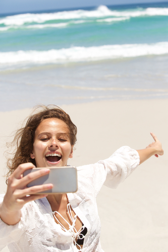 Portrait of a young woman taking selfie and pointing to the sea