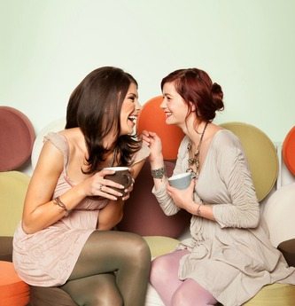 two young beautiful caucasian girls sitting on colorful sofa with coffee mugs in their hands, laughing